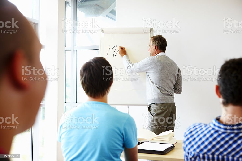 teacher writing on white board in classroom royalty-free stock photo