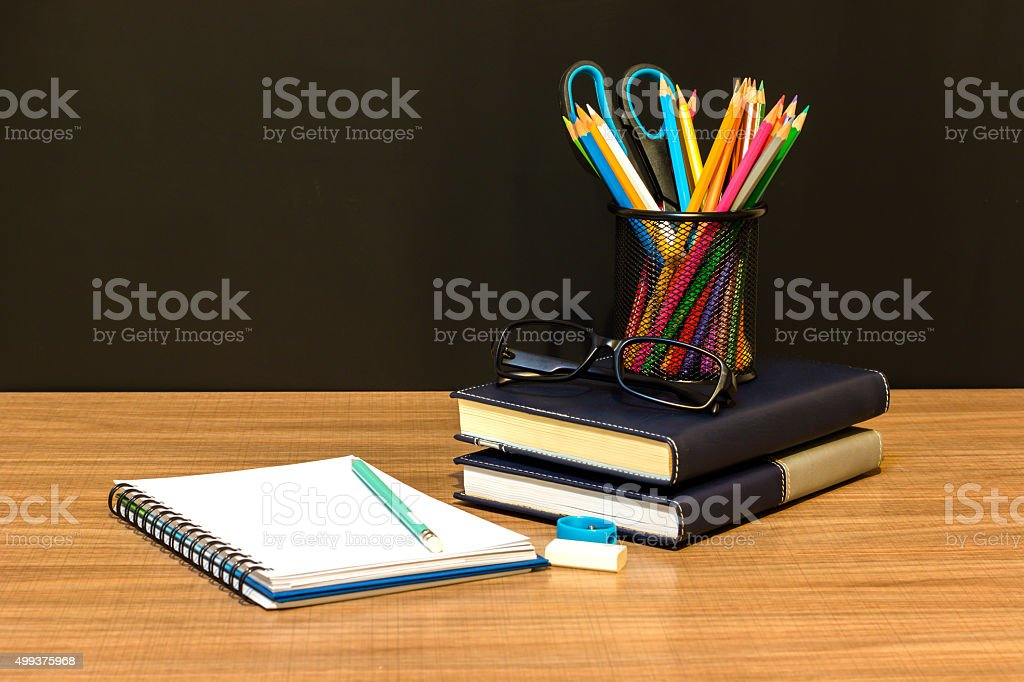 Teacher's desk with a color pencil, notebook and other equipment. stock photo