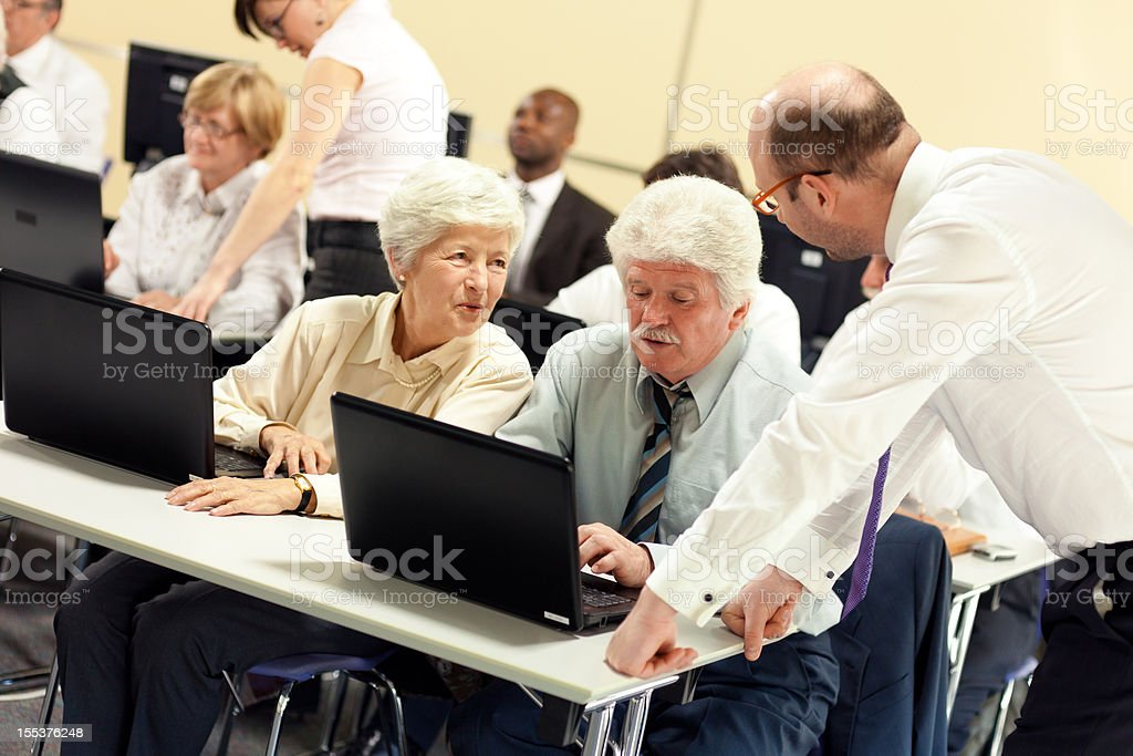 Teachers Explaining New Computer Technology to Senior Couple royalty-free stock photo