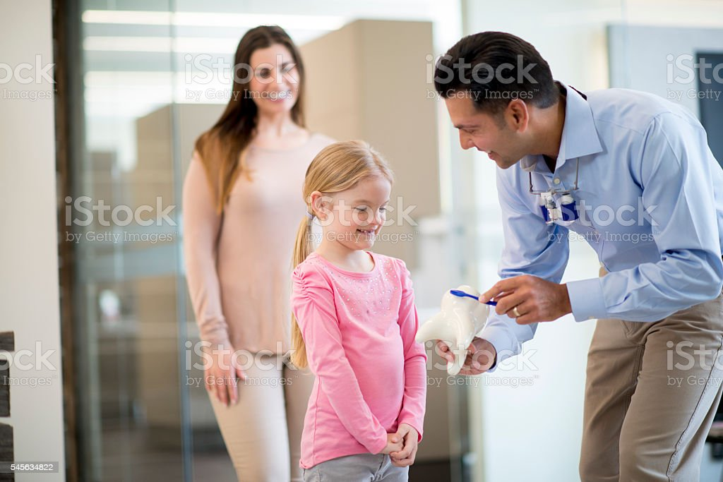 Teaching a Child How to Brush Her Teeth stock photo