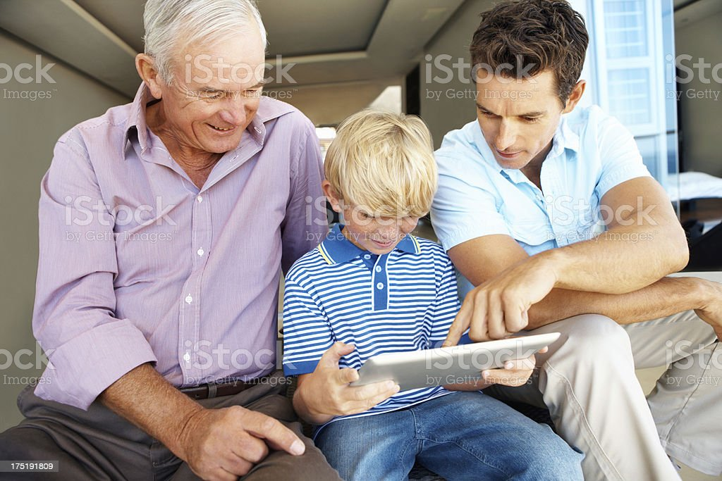 Teaching him how the tablet works royalty-free stock photo