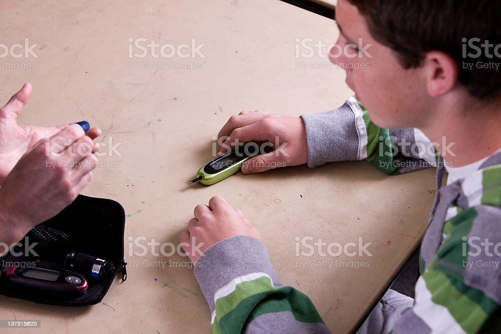 Teaching Teenager How To Perform Blood Sugar Test royalty-free stock photo