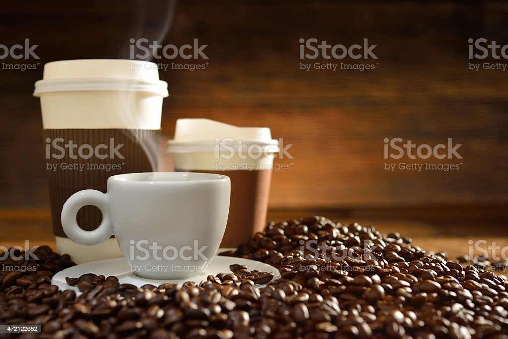 Teacup and saucer and takeaway cups amongst coffee beans stock photo
