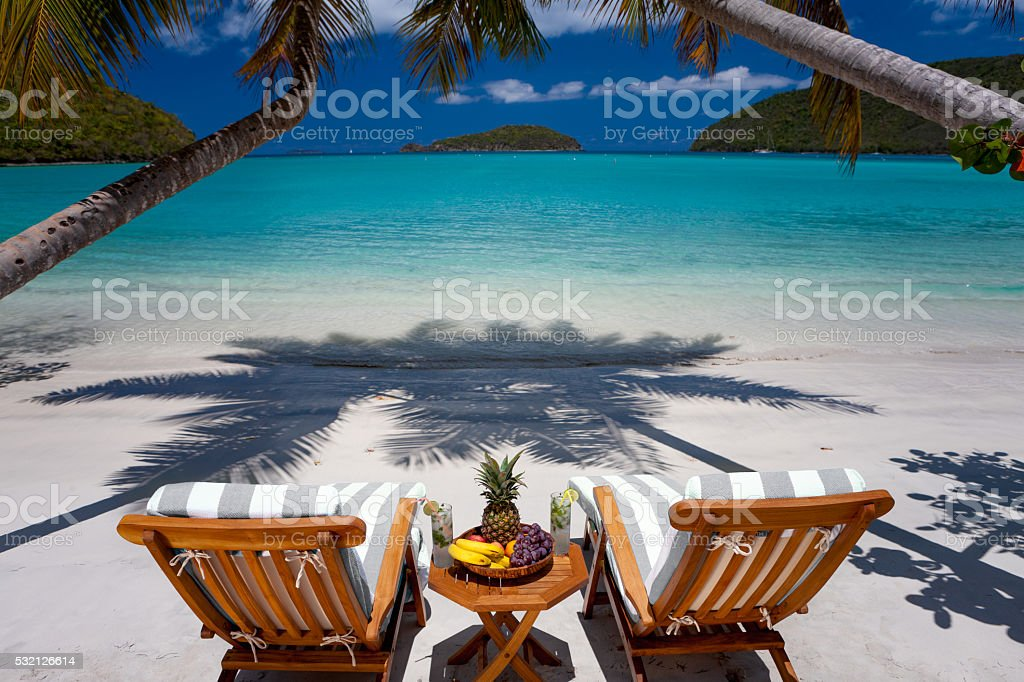 teak chairs under palm trees at perfect beach stock photo