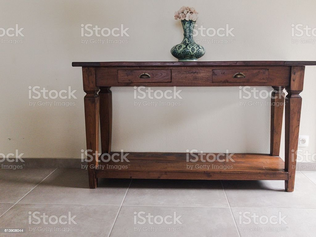 Teak wooden side tavble with drawers and ornamental vase stock photo