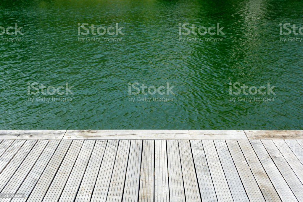 Teak wooden terrace and green water. stock photo