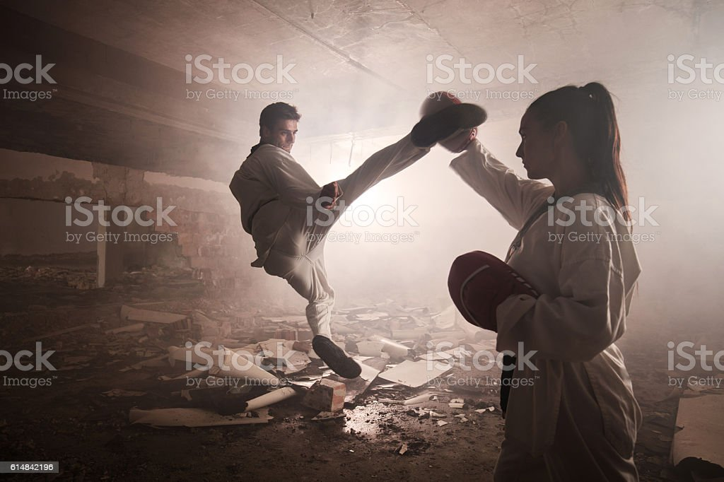 Teakwondo fighter practicing jump kick with help of sparring partner. stock photo