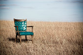 teal chair in a field with sky