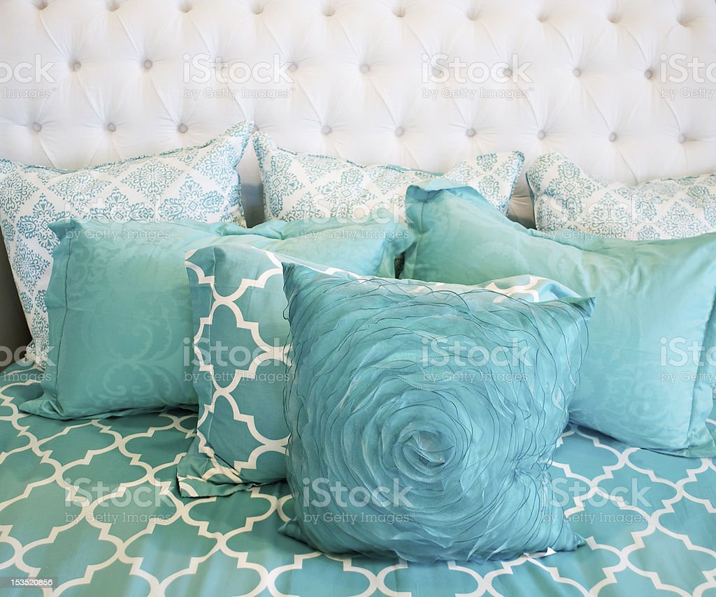 Teal cushions and bedding textiles stock photo