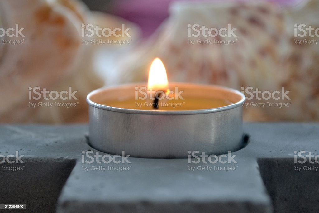 Tealight candle in zen setting with grey concrete holder stock photo