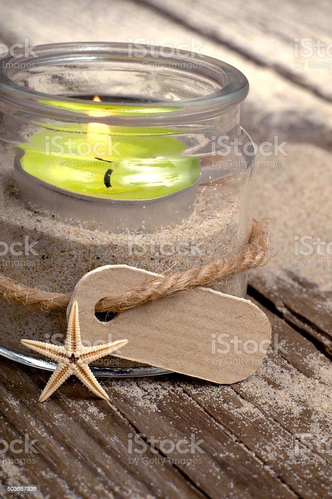 Tealight glass on a sandy ground stock photo