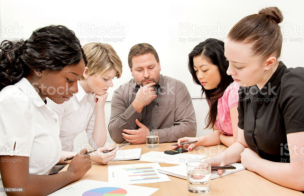 Team business meeting looking at graphs stock photo