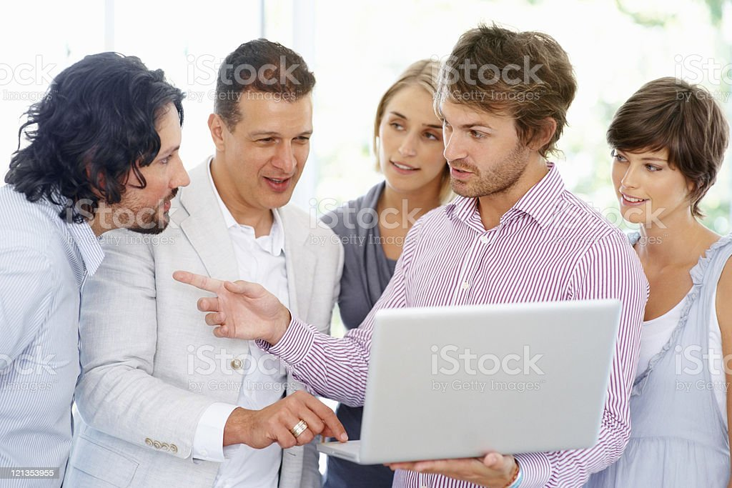 Team discussing project while viewing laptop royalty-free stock photo