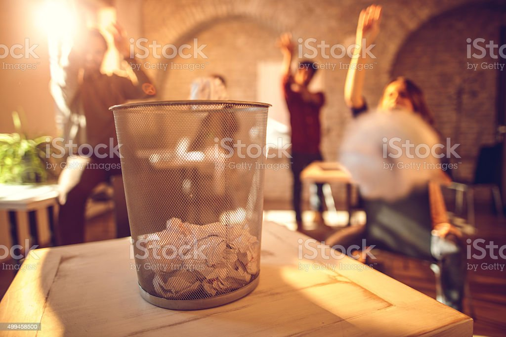 Team having fun while throwing crumpled papers in garbage can. stock photo