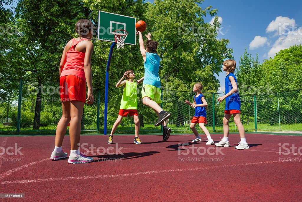 Team in colorful uniforms playing basketball game stock photo