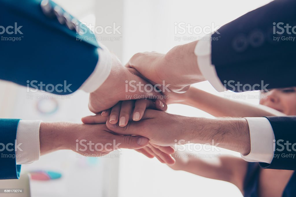 team in putting their hands on  top of each other stock photo