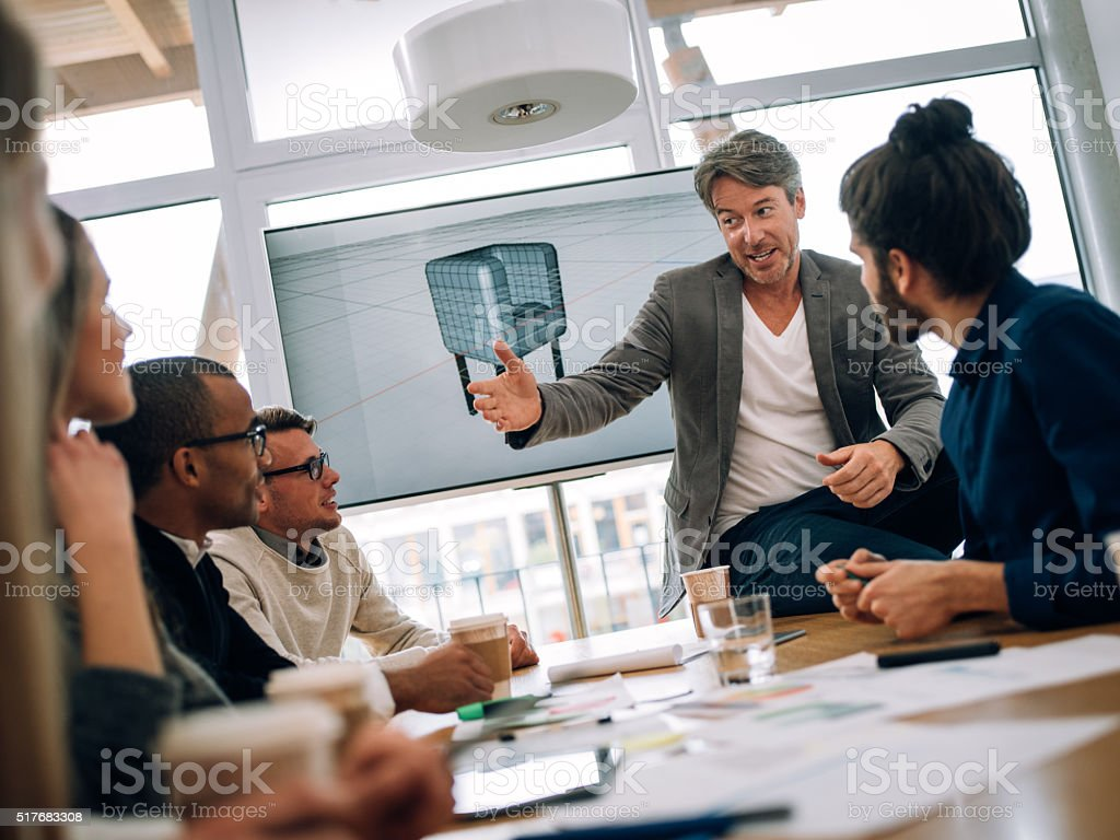 Team leader giving explanations to group  young multi-ethnic work colleugues stock photo