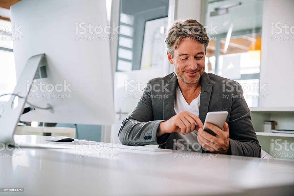 Mature team leader using his smartphone to text his team mates about...
