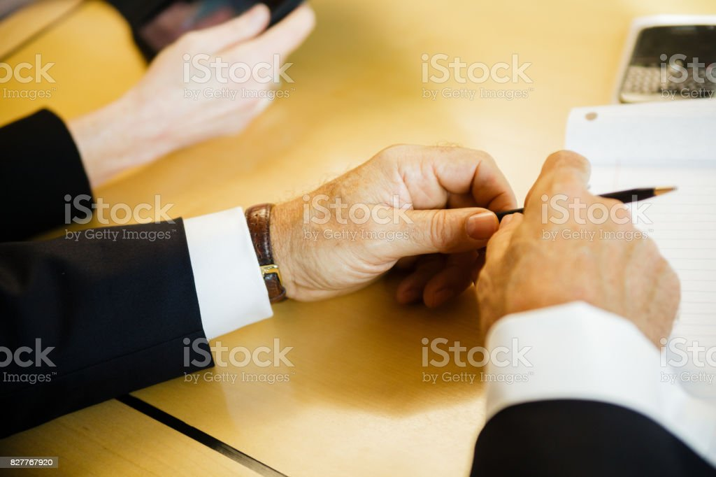 Team meeting in office around a wood conference table with notebook, smartphone and tablet stock photo