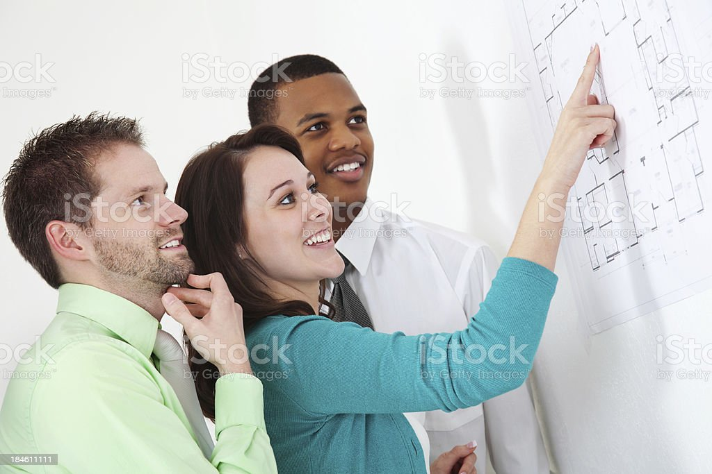 Team of architects looking at building plans together royalty-free stock photo