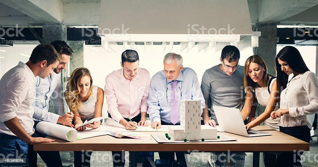Team of architects reviewing architectural model in the office. stock photo