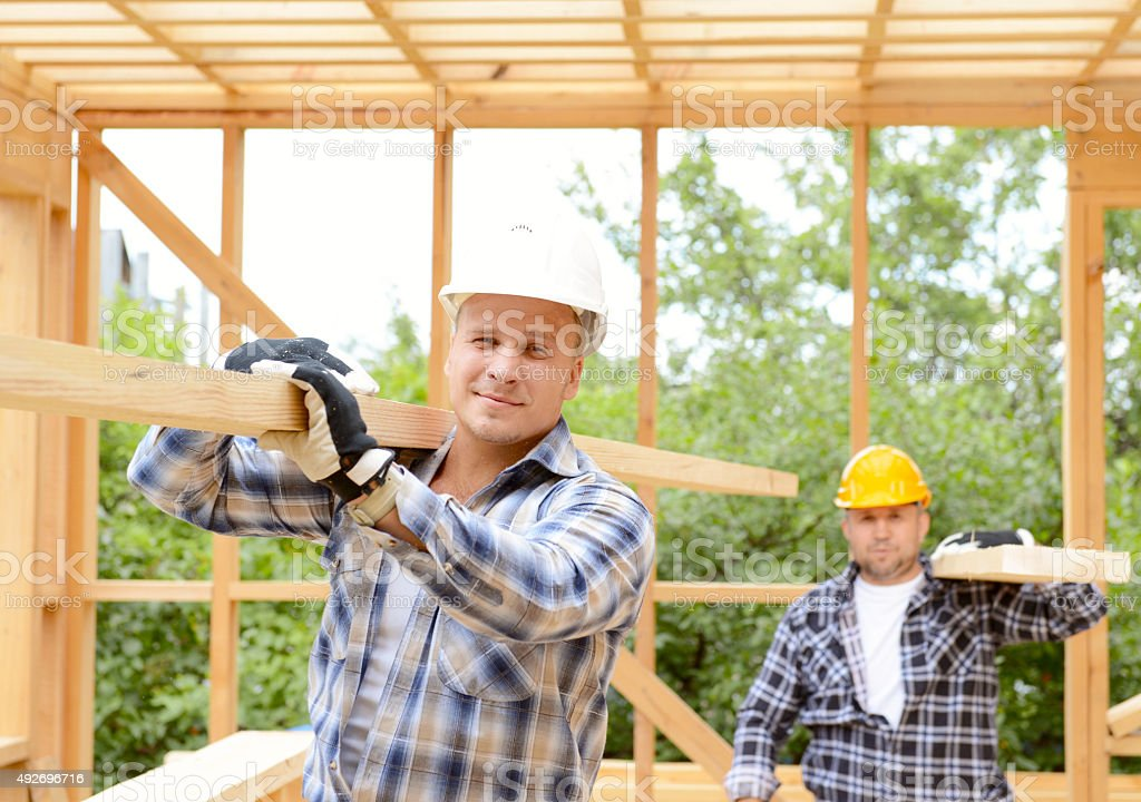 team of builders build frame house stock photo
