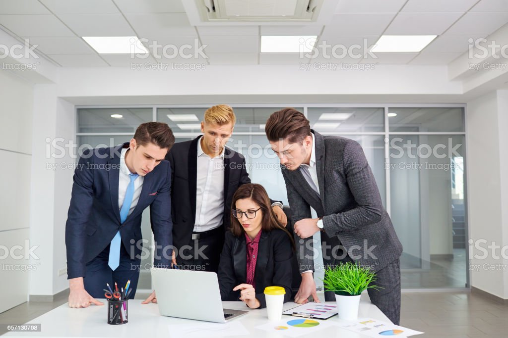 Team of business people work at a desk,smiling, laughing in mode stock photo