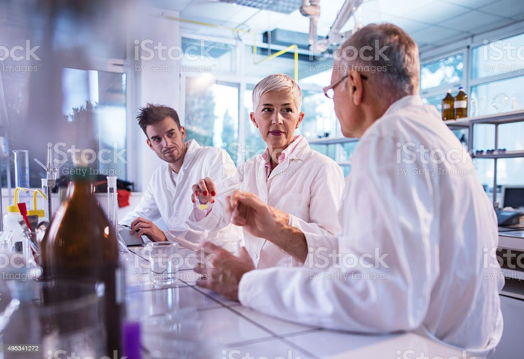 Team of chemists cooperating while working on a new research. stock photo