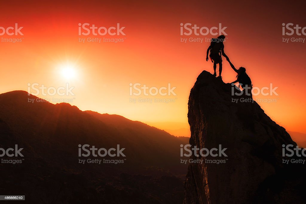 Team of climbers help to conquer the summit stock photo