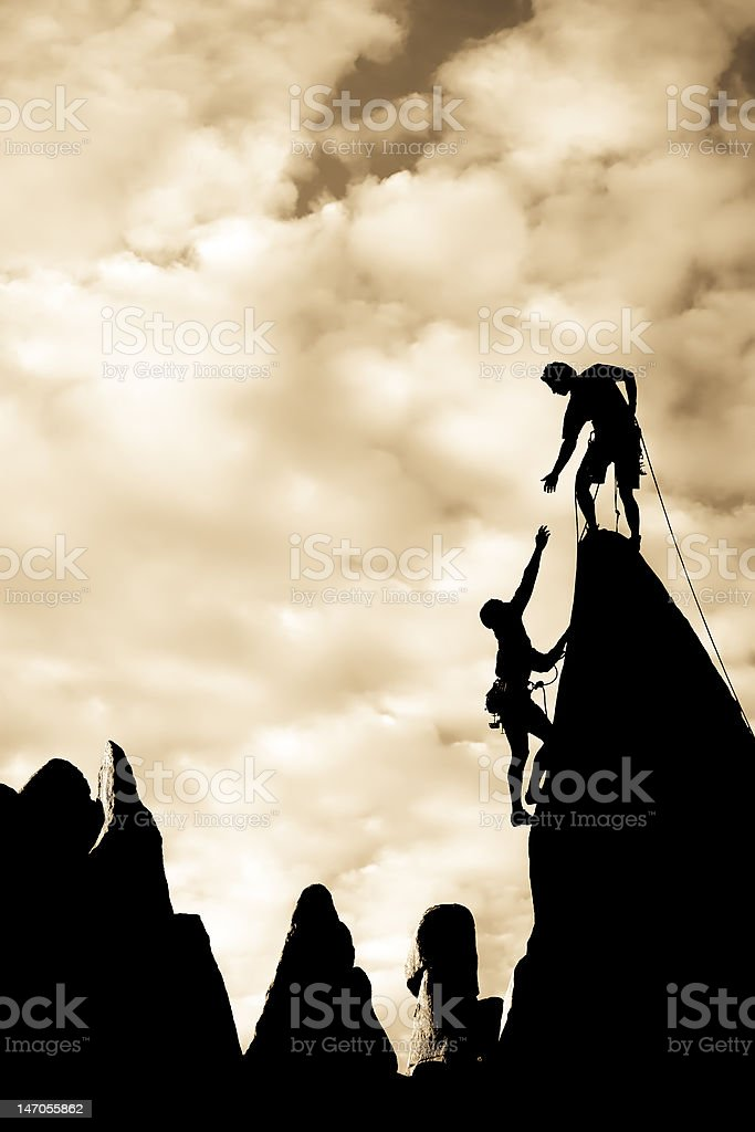 Team of climbers reaching the summit. stock photo
