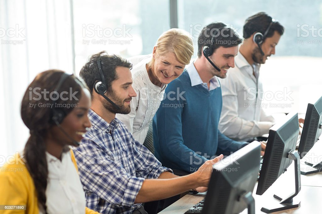 Team of colleagues working at their desk with headset stock photo