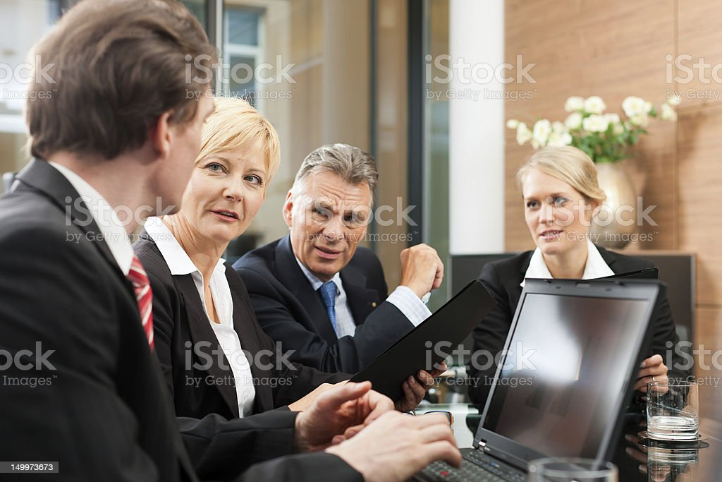 A team of coworkers chatting at a business meeting stock photo