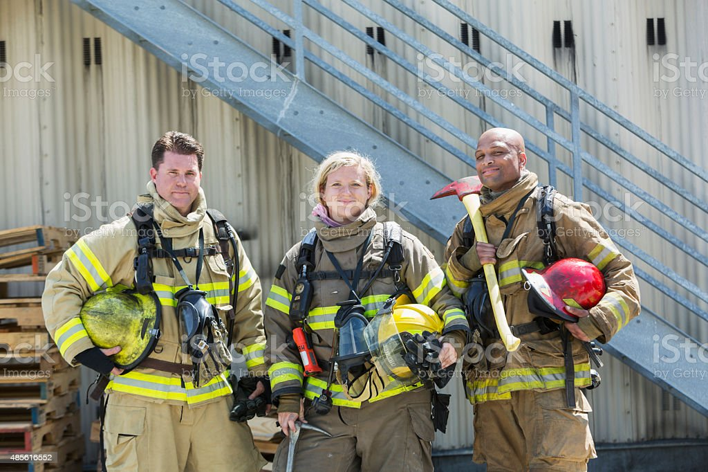Team of diverse firefighters with protective gear stock photo