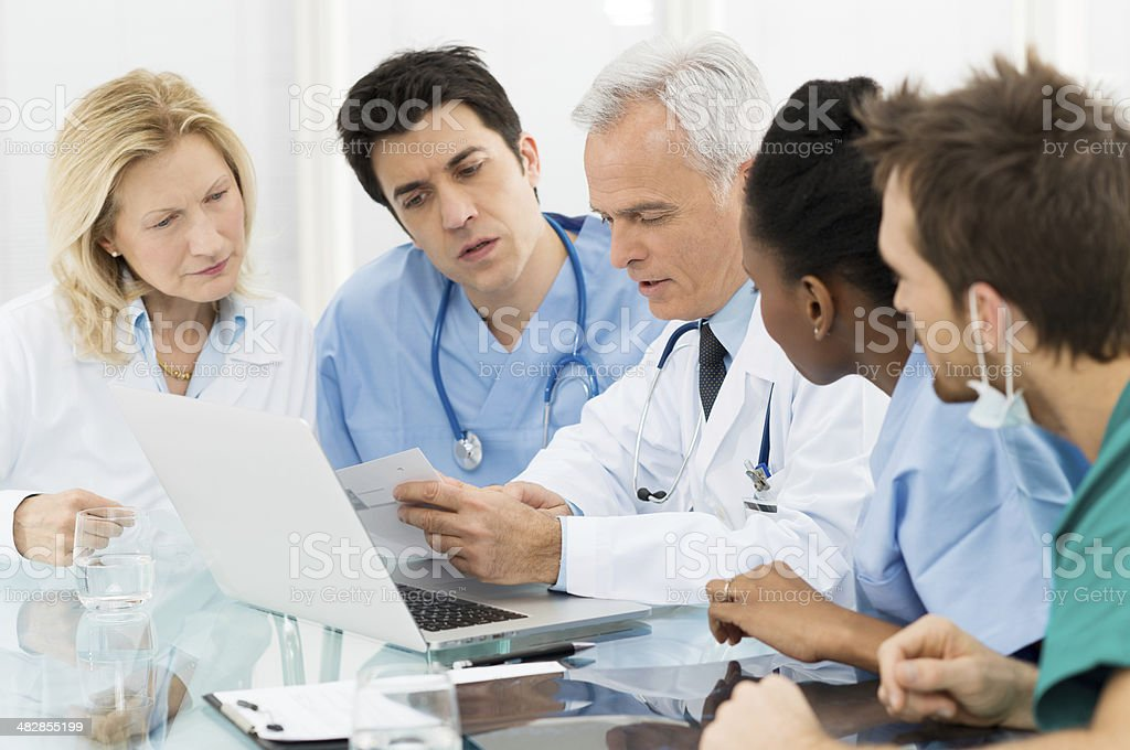 Team Of Doctors Examining Reports stock photo