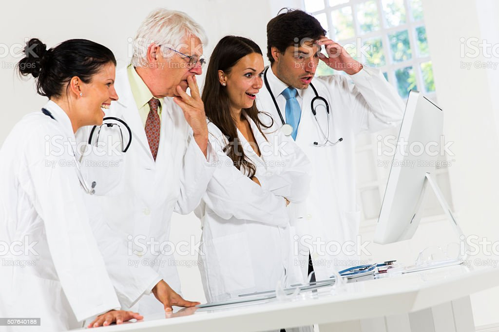 Team of doctors working in laboratory....loking at computer monitor stock photo