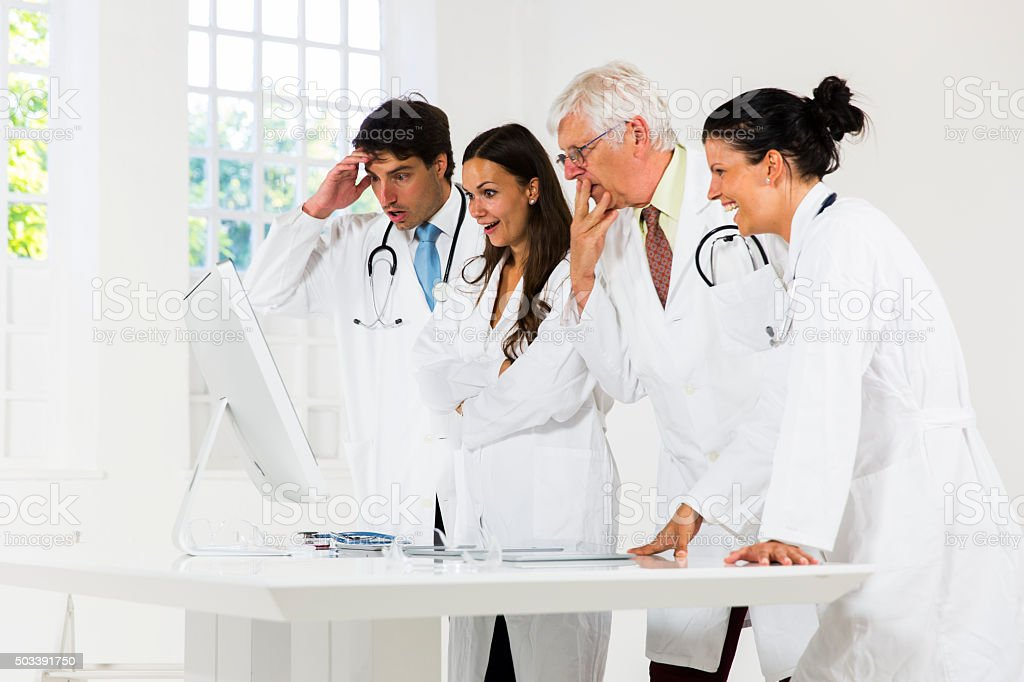 Team of doctors working in laboratory....loking at computer monitor,astronished stock photo