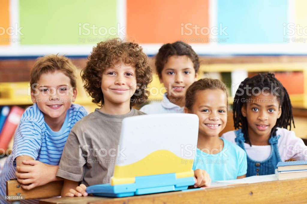 Team of elementary students using laptop royalty-free stock photo
