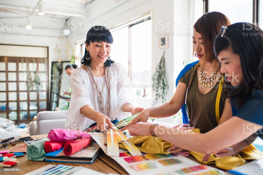 Team of fashion designers looking at colour swatches stock photo