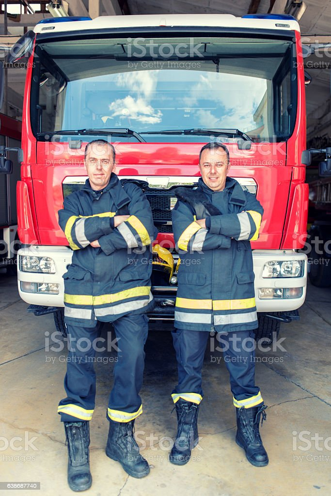 Team of firefighters in front of fire engine stock photo