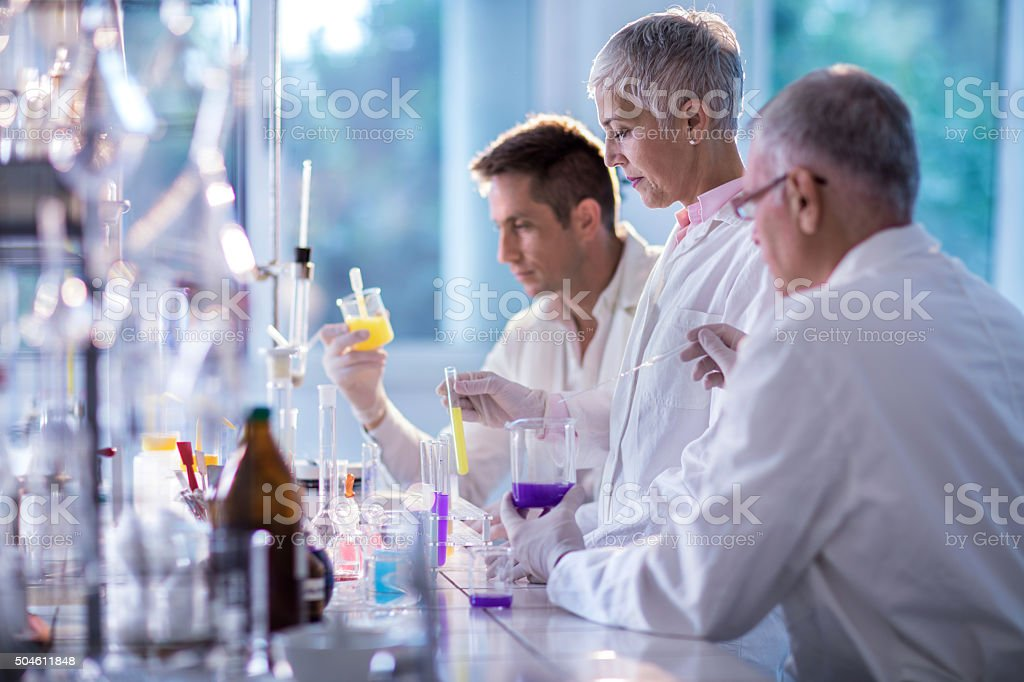 Team of forensic scientists working on an experiment in laboratory. stock photo