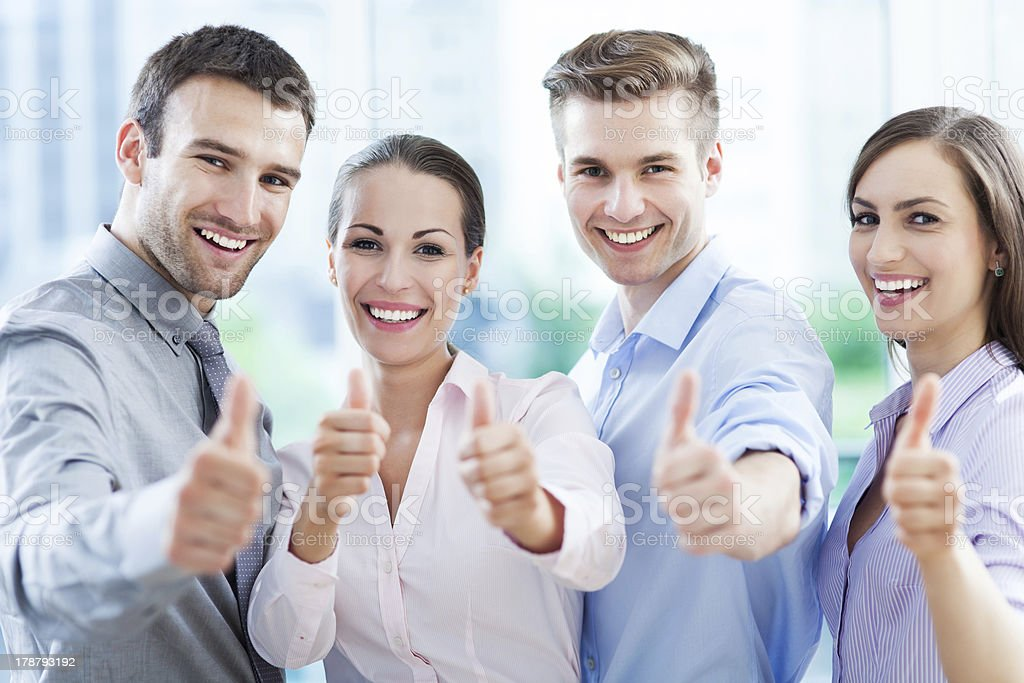 Team of four smiling business people giving thumbs up royalty-free stock photo