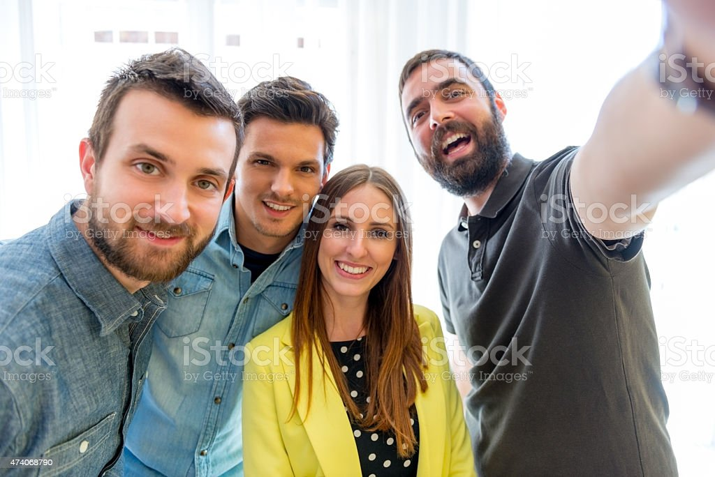 Team of four taking a selfie together stock photo