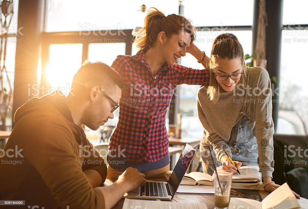 Team of happy college students cooperating while studying for exams. stock photo