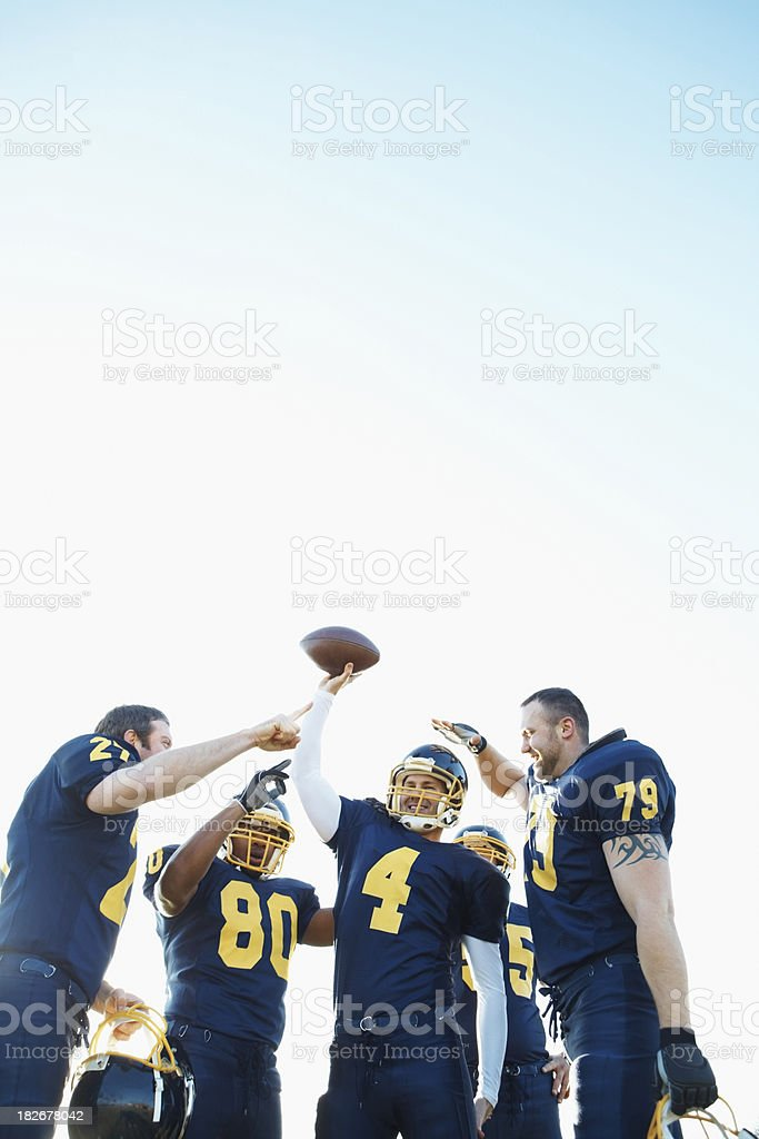 Team of happy footballers celebrating a victory against sky royalty-free stock photo