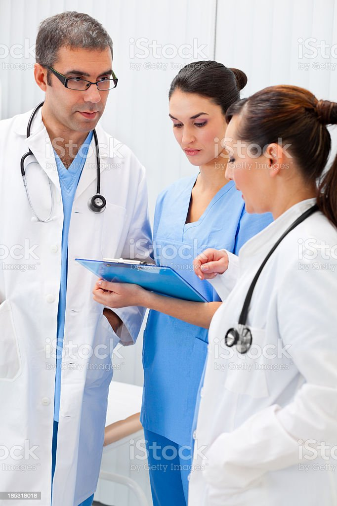 Team of healthcare professionals analyzing medical records royalty-free stock photo