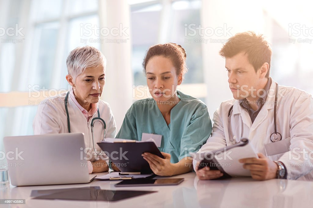 Team of healthcare workers reading medical documents together. stock photo