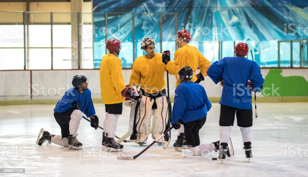 Team of ice hockey players talking about the strategy before a match. stock photo