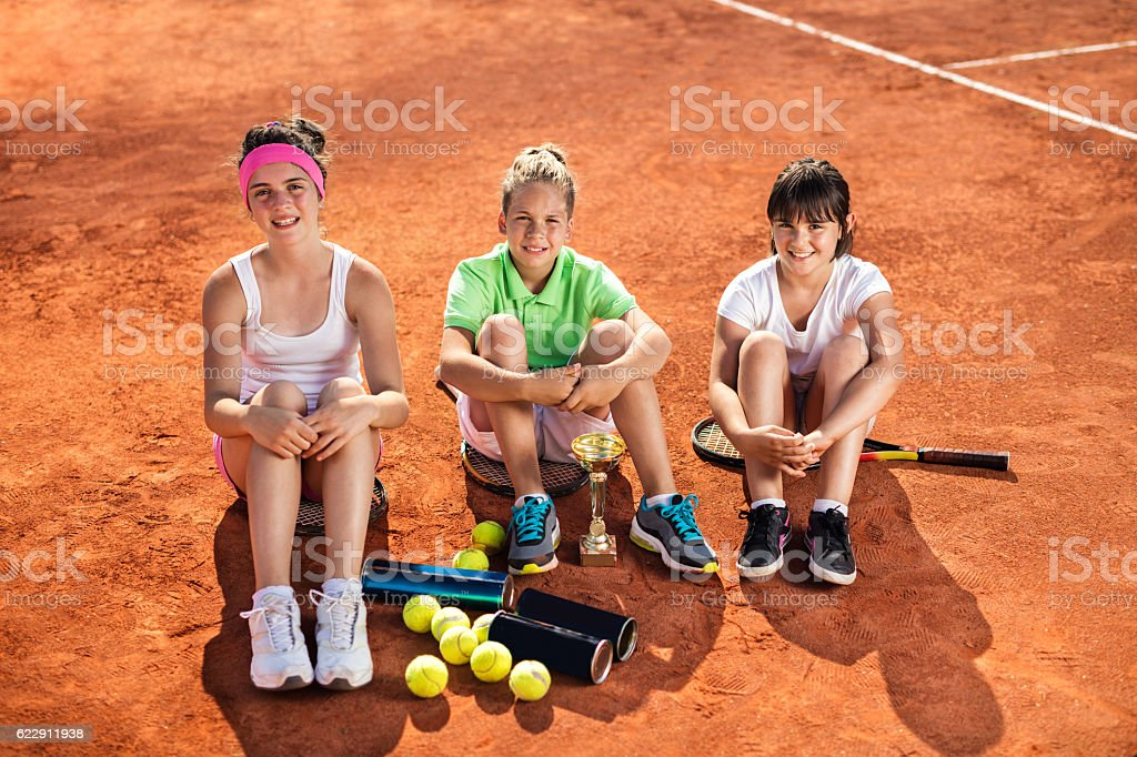 Team of little tennis players relaxing on tennis court. stock photo