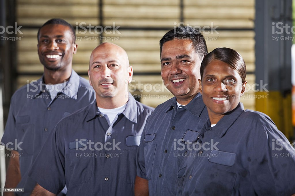 Team of mechanics in dark gray uniforms stock photo