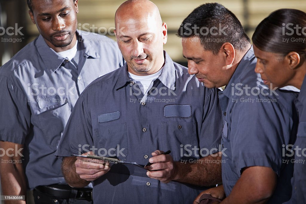 Team of mechanics looking at clipboard royalty-free stock photo